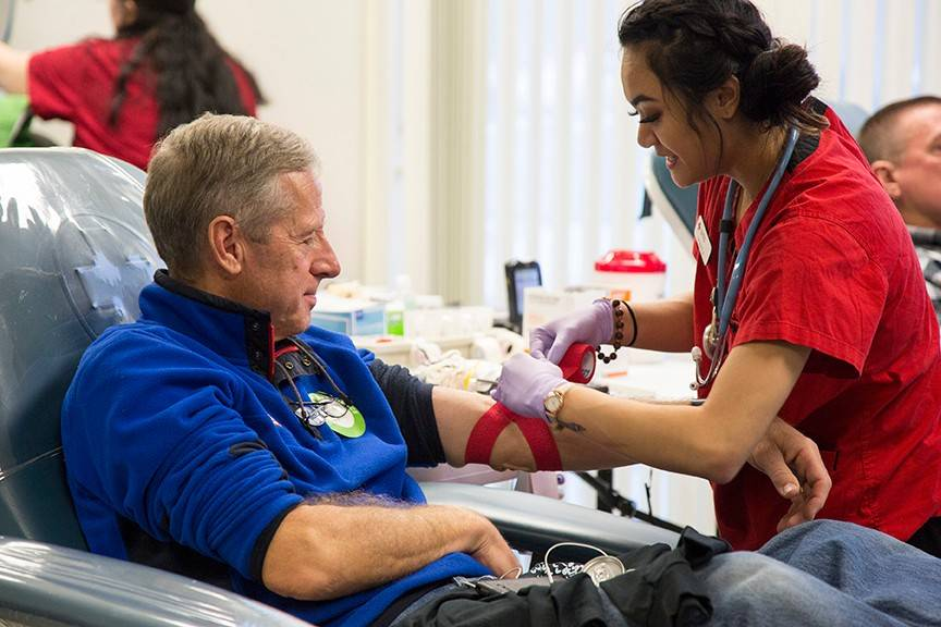 "American Red Cross staff member Deshayla Tran finishes collecting a whole blood donation from Terry Smith. Smith has been a regular blood donor for the last 5-10 years, and says, ""I keep getting emails saying that the Red Cross needs what I've got!"""