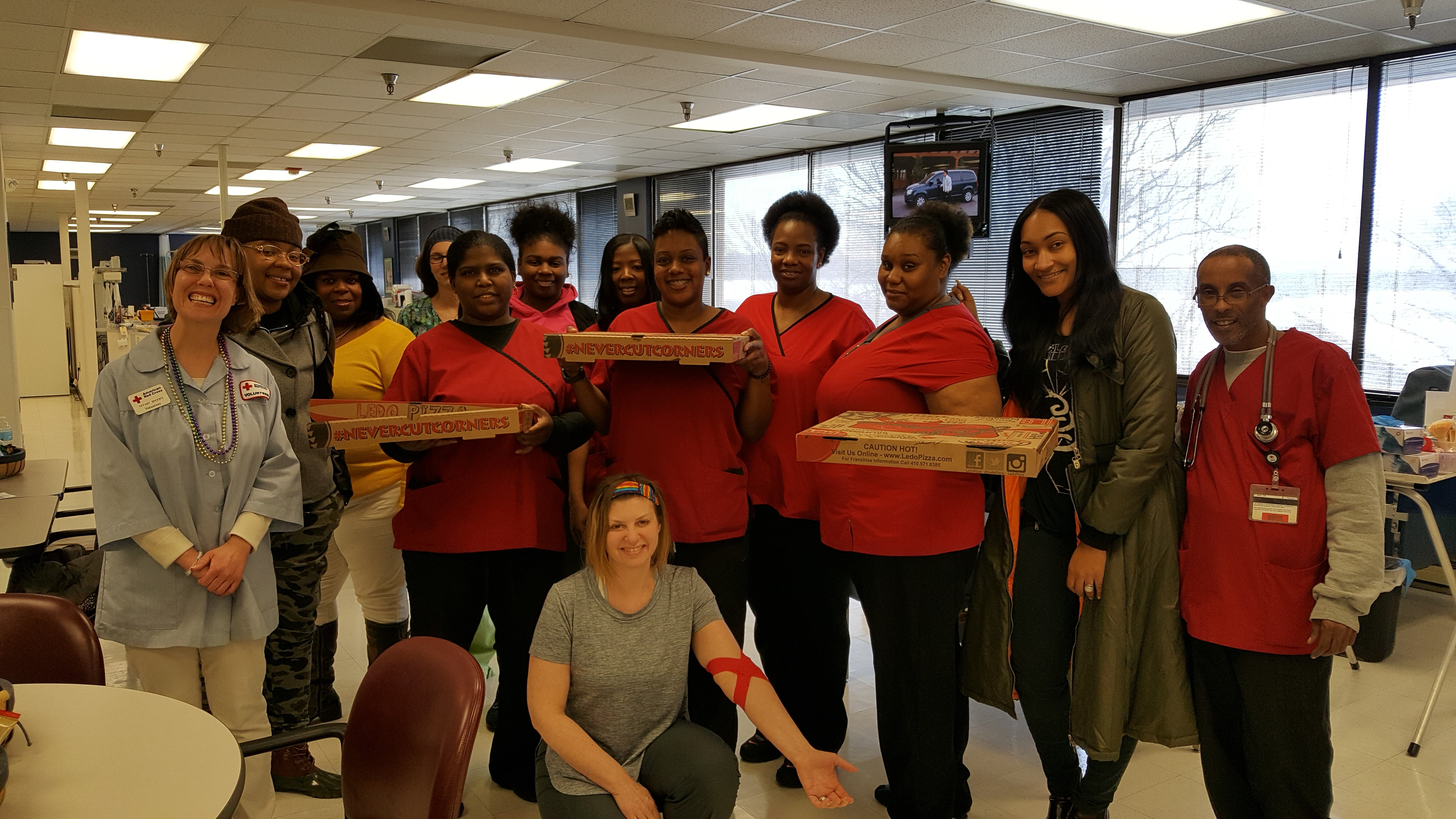 The Columbia Donation Center staff poses with Persia Nicole of the Ko Show and their Ledo's pizza.
